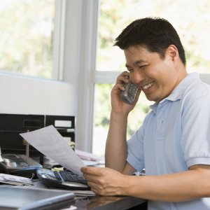 Man smiling on the phone while holding copy of his phone bill